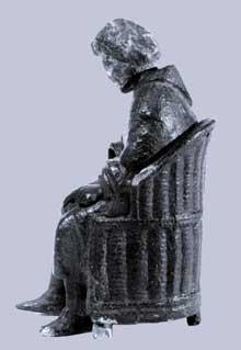 Statuette en bronze représentant un personnage barbu assis dans un fauteuil d'osier. La tête est amovible ainsi que le bras droit perdu. Trouvé à l'évêché, 16 rue brûlée. Musée archéologique de Strasbourg