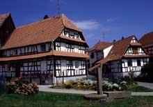 Betschdorf: deux belles maisons traditionnelles que précède un puits à balancier. (La maison alsacienne)