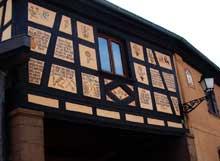 Dauendorf en pays de Hanau: portail surbâti de ferme avec décors modernes imitant le style traditionnel, réalisés en 1986. (La maison alsacienne)