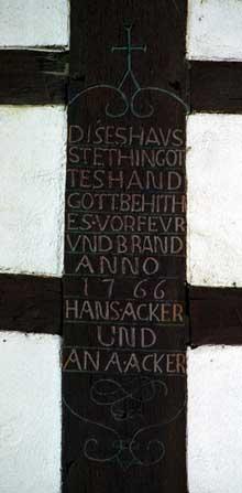 """Weyersheim. """"Cette maison se tient dans la main de Dieu. Que Dieu la protège du feu et de l'incendie. 1766. Jean Acker et Anna Acker». Cartouche. (La maison alsacienne)"""