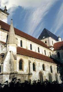 Beauvais, église saint Etienne: vue générale de l'extérieur roman. La construction à Beauvais d'une église communale dédiée à Saint Etienne date de la fin du Xe siècle. La construction de l'église romane date de 1120. Nef et façade sont achevées au XIIIe siècle. La nef est un exemple de transition entre le roman et le gothique. Le roman est présent dans les arcs en plein cintre des tribunes aveugles des fenêtres hautes. Le gothique fait son apparition dans les croisées d'ogives qui soutiennent les voûtes quadripartites