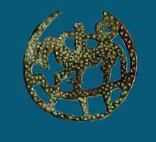 Rouelle figurant un cavalier tenant une couronne Symbolisant le Christ. Fin du VIè. Bronze moulé, 6,8cm. Saint Germain en Laye, musée d'Archéologie nationale