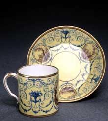 Tasse litron en porcelaine tendre à fond jaune pâle. Sèvres, 1788. Décor de guirlandes et de paysages en camaïeu bistre. 6,5 cm