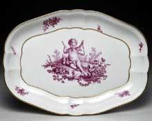 Plateau ovale en porcelaine tendre de Sèvres à décor en camaïeu rose au centre d'un enfant jouant du triangle, d'après Boucher. Marqué, lettre date G pour 1759-1760, marque de peintre Buteux l'aîné (1756-1782). Longueur: 28,9 cm