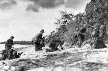 15 juin 1944 : débarquement à Saipan : deux « Marines » viennent d'être touchés par des tireurs japonais